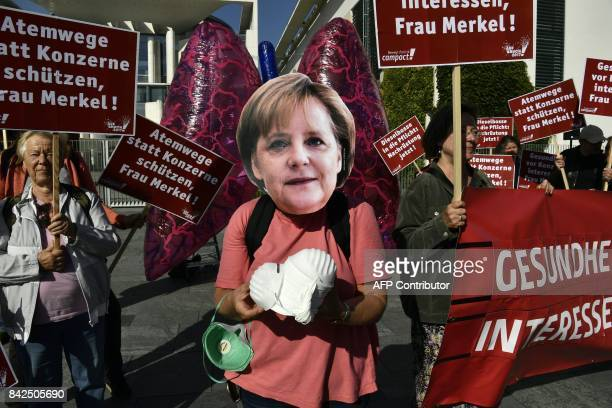 A demonstrator wearing a mask featuring a likeness of German Chancellor Angela Merkel distributes pollution masks during a protest outside the...