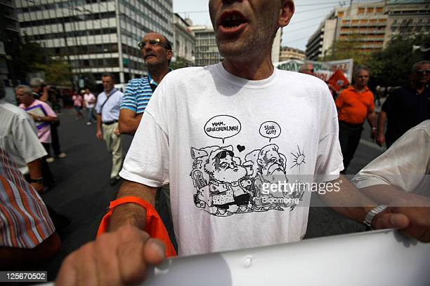 A demonstrator wearing a political cartoon on his tshirt shouts during a protest by public sector unionists against government cuts in Athens Greece...