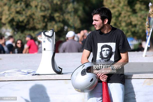 A demonstrator wearing a teeshirt bearing a picture of Cuban revolutionary Che Guevara sits during a protest against new government austerity bill...