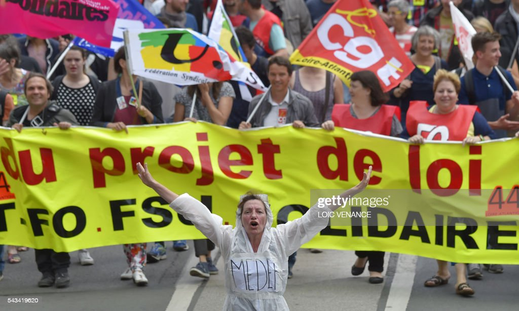 A demonstrator wearing an outfit reading 'Medef' (French employer federation), gestures ahead of people taking part in a protest against controversial labour reforms, on June 28, 2016 in Nantes, western France. People took to the streets in France on June 28 in the latest protest march in a marathon campaign against the French Socialist government's job market reforms. Last month the government used a constitutional manoeuvre to push the bill through the lower house without a vote in the face of opposition from Socialist backbenchers. / AFP / LOIC