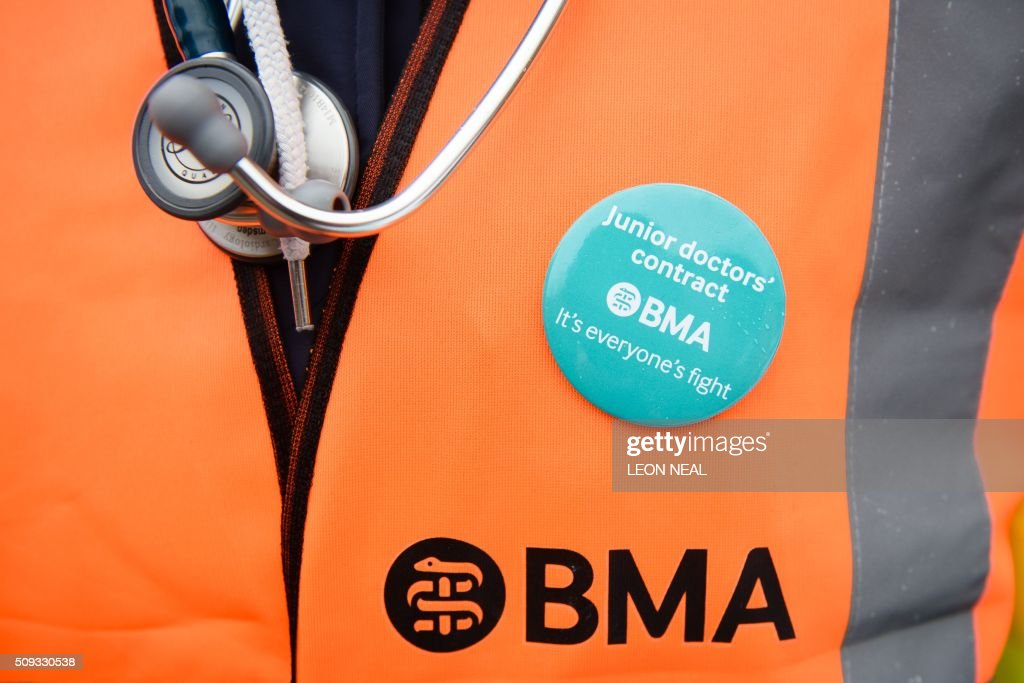 A demonstrator wears a BMA (British Medical Association) badge alongside her stethoscope outside the Royal Free hospital in north London on February 10, 2016 during a 24-hour junior doctors strike over pay and conditions. Thousands of junior doctors began a second strike at English hospitals on Wednesday against proposed new working conditions and pay rates. Junior doctors -- all medics below consultant level -- were providing emergency care only from 8:00am (0800 GMT) in the 24-hour strike. NEAL
