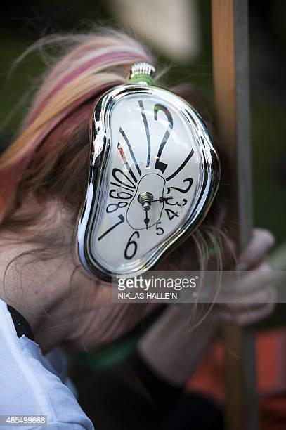 A demonstrator wears a clock as headdress as she takes part in The People's Climate march in central London on March 7 2015 Around 5000 protesters...