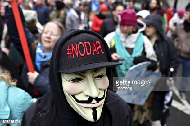 A demonstrator wears a Guy Fawkes mask and #NODAPL hat while participating in a protest against the Dakota Access Pipeline in Washington DC US on...