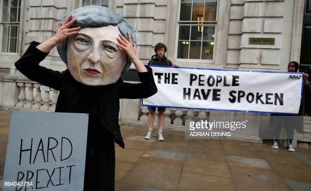 A demonstrator wears a mask depicting Britain's Prime Minister and leader of the Conservative Party Theresa May poses with a mock gravestone bearing...