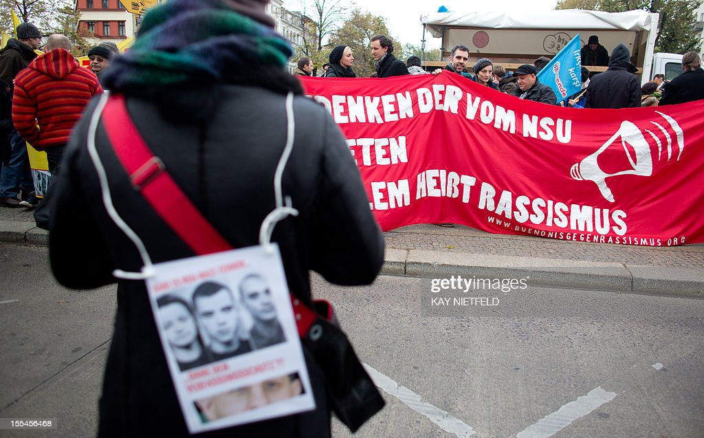 A demonstrator wears a poster with the portraits of the alleged committers of a murder spree targeting immigrants during a protest march against racism on November 4, 2012 in Berlin. Twelve months after revelations that a neo-Nazi trio was likely behind the seven-year murder spree in which nine men of Turkish and Greek origin and a German policewoman were killed, Germany has sought to mend security flaws but the trauma still reverberates.