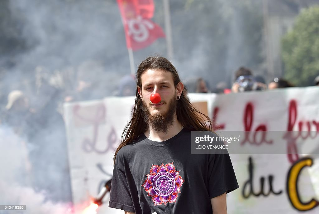 A demonstrator wears a red nose during a protest against controversial labour reforms, on June 28, 2016 in Nantes, western France. People took to the streets in France on June 28 in the latest protest march in a marathon campaign against the French Socialist government's job market reforms. Last month the government used a constitutional manoeuvre to push the bill through the lower house without a vote in the face of opposition from Socialist backbenchers. / AFP / LOIC
