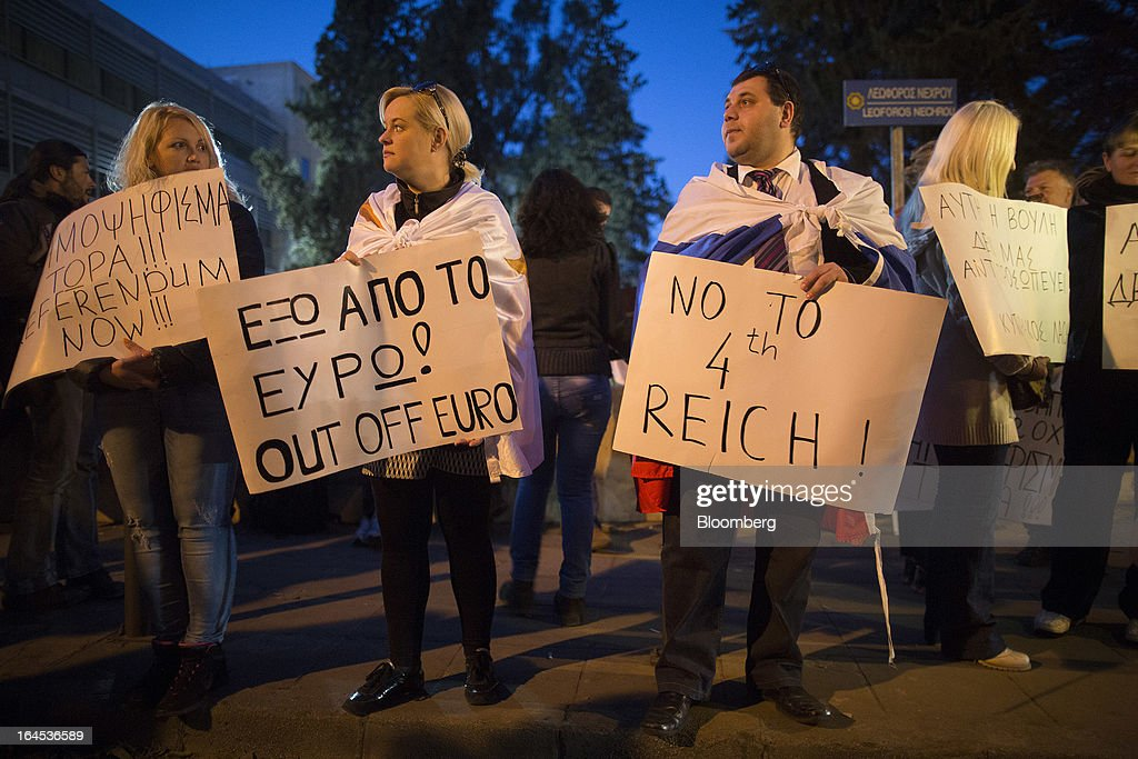 A demonstrator wears a Russian flag and carries a banner reading 'no to the 4th Reich' as he protests outside the Cypriot parliament in Nicosia, Cyprus, on Sunday, March 24, 2013. Cyprus's fate hangs in the balance as euro-area finance ministers meet today to decide whether the tiny Mediterranean island has done enough for a bailout that will avert its financial collapse. Photographer: Simon Dawson/Bloomberg via Getty Images
