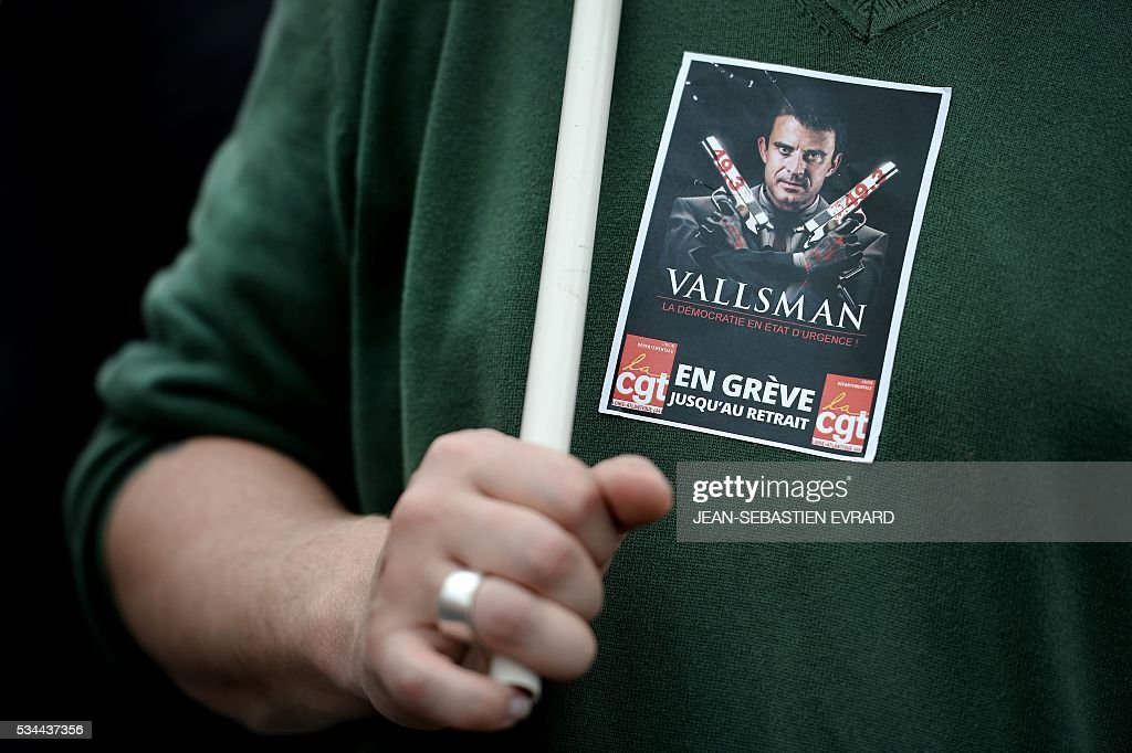 A demonstrator wears a sticker featuring France's Prime Minister Manuel Valls on May 26, 2016 in Nantes, western France, during a protest against government planned labour law reforms. The French government's labour market proposals, which are designed to make it easier for companies to hire and fire, have sparked a series of nationwide protests and strikes over the past three months. Masked youths clashed with police and striking workers blockaded refineries and nuclear power stations on May 26 as an escalating wave of industrial action against labour reforms rocked France. / AFP / JEAN