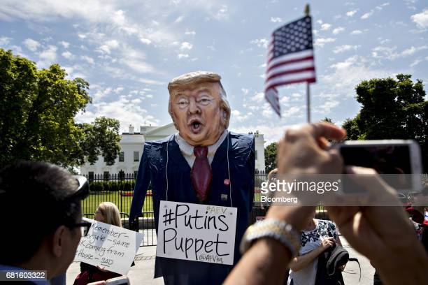 A demonstrator wears an effigy in the likeness of US President Donald Trump with a sign that reads 'Putins Puppet' during a protest outside the White...