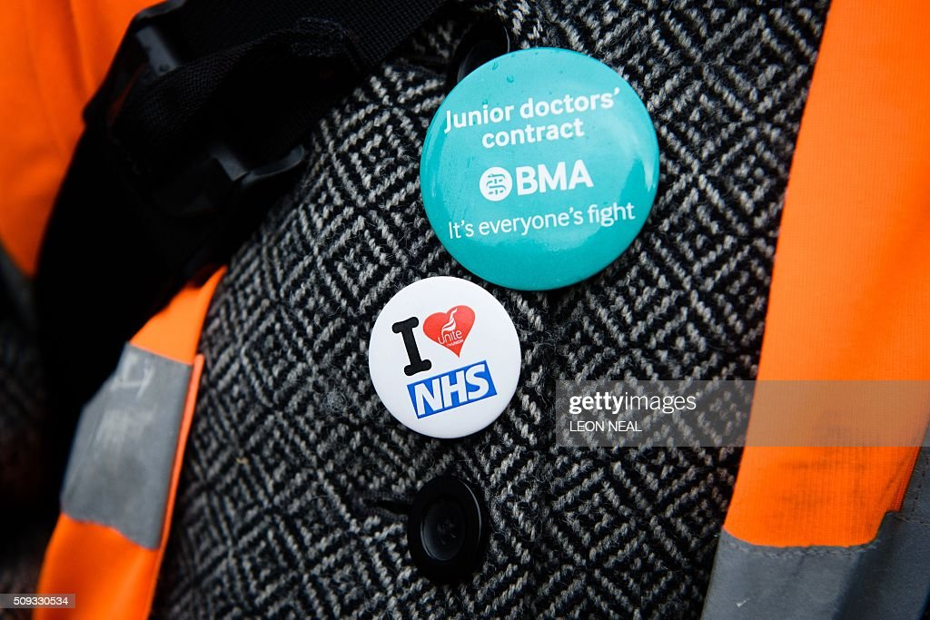 A demonstrator wears pro-NHS badges outside Whittington hospital in north London on February 10, 2016 during a 24-hour junior doctors strike over pay and conditions. Thousands of junior doctors began a second strike at English hospitals on Wednesday against proposed new working conditions and pay rates. Junior doctors -- all medics below consultant level -- were providing emergency care only from 8:00am (0800 GMT) in the 24-hour strike. NEAL