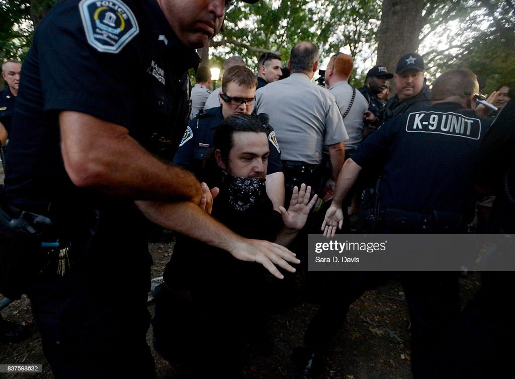 A demonstrator who partially covered his face with a bandana is arrested by police during a rally for the removal of a Confederate statue, coined Silent Sam, on the campus of the University of Chapel Hill on August 22, 2017 in Chapel Hill North Carolina.