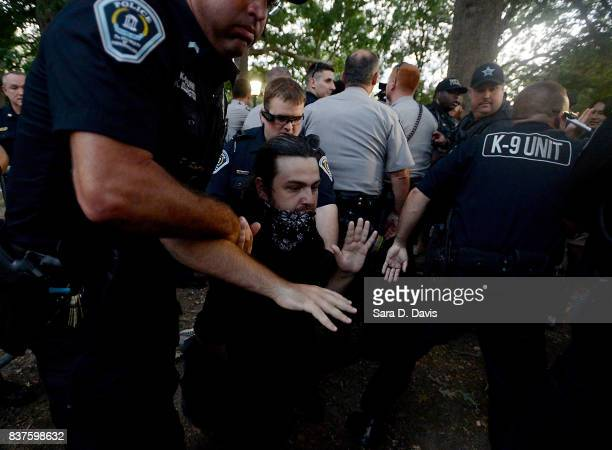 A demonstrator who partially covered his face with a bandana is arrested by police during a rally for the removal of a Confederate statue coined...