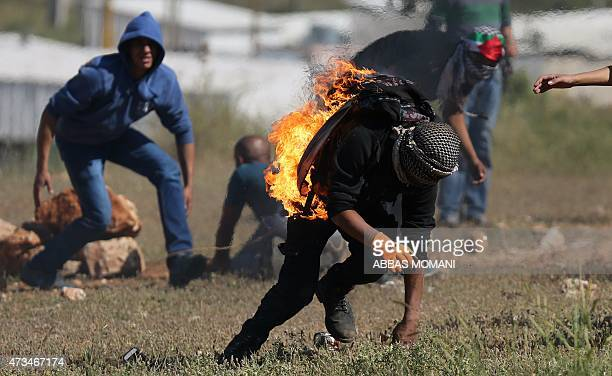 A demonstrator who set himself on fire after misthrowing a molotov cocktail reacts during clashes with Israeli security forces following a...