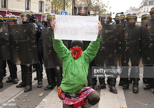 A demonstrator with a costume holds a poster in front of the police during the forbidden COP21 demonstration at Republique Square in Paris France on...