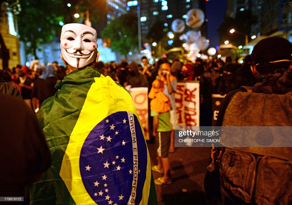 A demonstrator with a Guy Fawkes mask is pictured as clashes with the riot police erupt after a march by Brazilian workers in Rio de Janeiro on July 11, 2013 in a day of industrial action called by major unions to press demands for better work conditions. Demonstrators on Thursday blocked roads and staged protest rallies across the country on the 'National Day of Struggles' which was called by the country's five leading labour federations during last month's mass street protests to demand better public services and an end to endemic corruption. AFP PHOTO / CHRISTOPHE SIMON