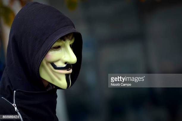 A demonstrator with Guy Fawkes's mask is pictured during the demonstration against the G7 meeting in Turin