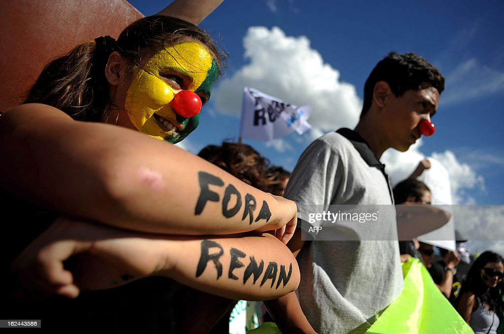 A demonstrator with her face painted and her arms reading 'Out Renan' takes part in a protest against the president of the Brazilian Senate, Renan Calheiros, in front of the Brazilian National Congress, in Brasilia, on February 23, 2013. Calheiros was elected by his colleagues despite many corruption claims over him. An undersigned made on the internet with over then 1,5 million signatures was delivered by activists to the Senate this week, demanding his impeachment.