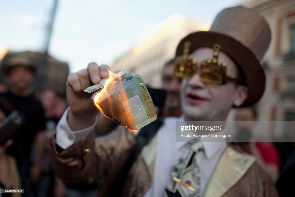 A demonstrator with Spain's Indignant movement dressed in costume representing a banker burns a Euro note during a rally at Puerta del Sol on May 15, 2012 in Madrid, Spain. Spain's Indignant movement has prepared events across Spain to mark the first anniversary of their movement, formed to protest against corruption in politics, the economic crisis and the high unemployment rate. The movement's anniversary coincides with Madrid's regional festivities.