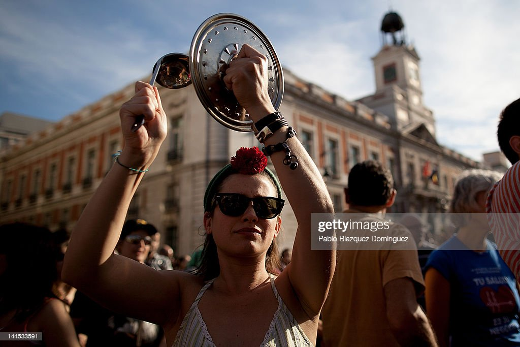 A demonstrator with Spain's Indignant movement hits a pan lid during a rally at Puerta del Sol on May 15, 2012 in Madrid, Spain. Spain's Indignant movement has prepared events across Spain to mark the first anniversary of their movement, formed to protest against corruption in politics, the economic crisis and the high unemployment rate. The movement's anniversary coincides with Madrid's regional festivities.