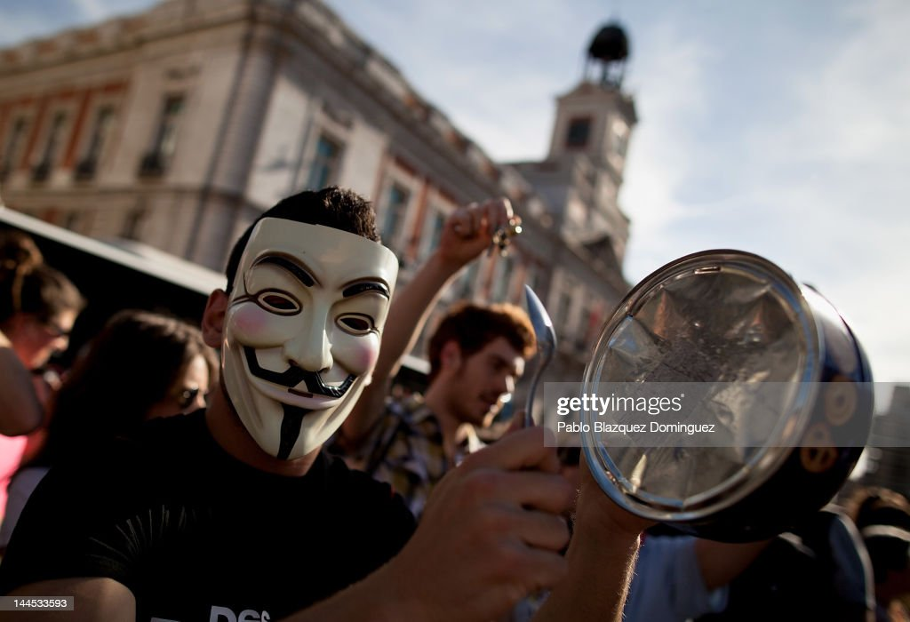 A demonstrator with Spain's Indignant movement wearing a Guy Fawkes mask hits a biscuit tin during a rally at Puerta del Sol on May 15, 2012 in Madrid, Spain. Spain's Indignant movement has prepared events across Spain to mark the first anniversary of their movement, formed to protest against corruption in politics, the economic crisis and the high unemployment rate. The movement's anniversary coincides with Madrid's regional festivities.