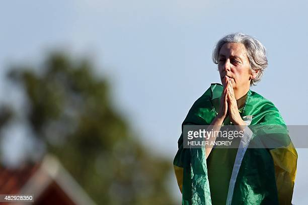 A demonstrator wrapped in a Brazilian flag waits for Brazilian former chief of staff Jose Dirceu outside the Federal Police headquarters in Curitiba...