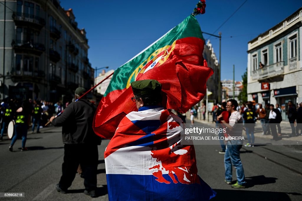 A demonstrator wrapped in a Cuban flag with Che Guevara passes by a Portuguese flag during the traditional May Day rally in Lisbon on May 1, 2016. Thousands of people demonstrated today in Lisbon and Portugal's main cities against the government's austerity measures. / AFP / PATRICIA