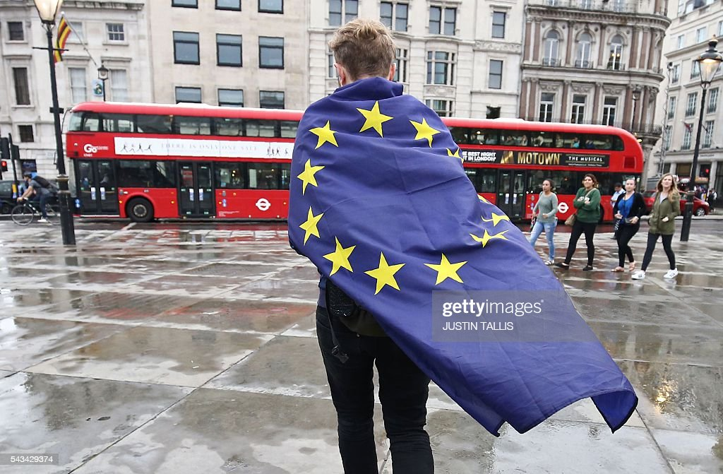 A demonstrator wrapped in a European flag leaves an anti-Brexit protest in Trafalgar Square in central London on June 28, 2016. EU leaders attempted to rescue the European project and Prime Minister David Cameron sought to calm fears over Britain's vote to leave the bloc as ratings agencies downgraded the country. Britain has been pitched into uncertainty by the June 23 referendum result, with Cameron announcing his resignation, the economy facing a string of shocks and Scotland making a fresh threat to break away. / AFP / JUSTIN
