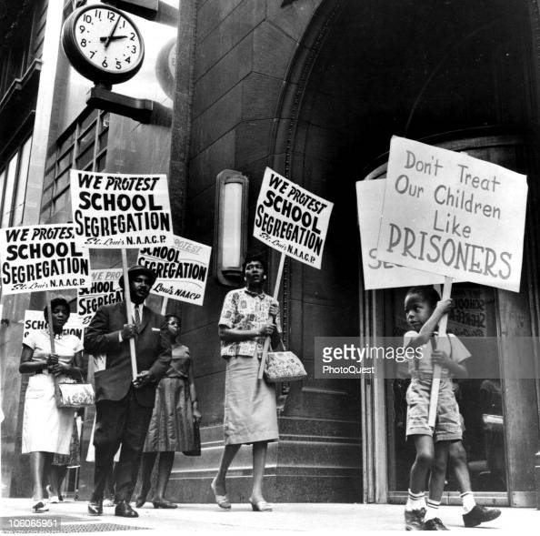 Demonstrators a young boy among them picket in front of a school board office in protest of segregation St Louis Missouri early 1960s