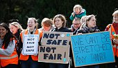 Demonstrators and Junior doctors hold placards as they protest outside the Basingstoke and North Hampshire Hospital in Basingstoke west of London on...