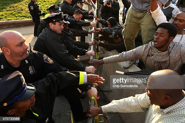 Demonstrators and police officers wrestle over a metal barricade during a protest against police brutality and the death of Freddie Gray outside the...