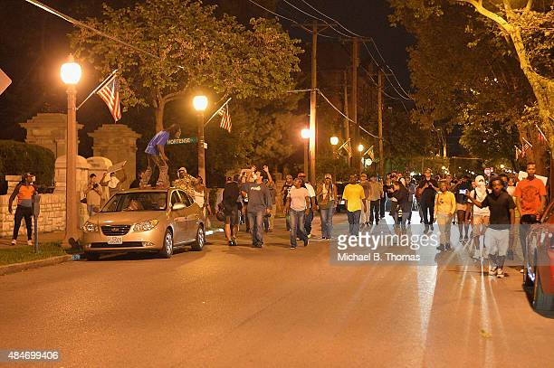 Demonstrators approach during a protest action through the Central West End of St Louis Missouri on August 20 2015 After a night of unrest sparked by...