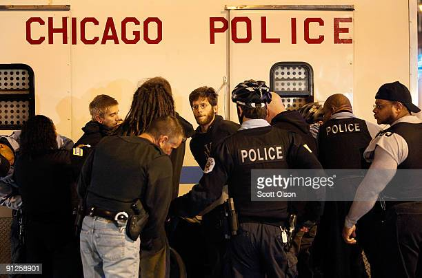 Demonstrators are arrested after interfering with city workers who were hanging an Olympic banner on the Picasso statue in Daley Plaza reflecting the...