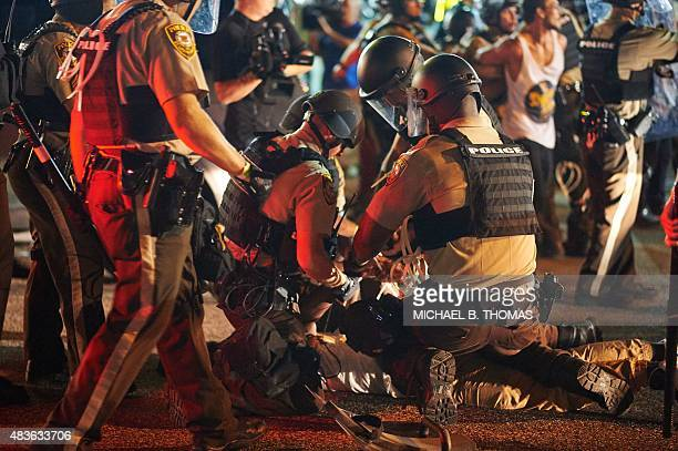Demonstrators are arrested by police during a civil disobedience action on August 10 2015 on West Florissant Avenue in Ferguson Missouri The night...