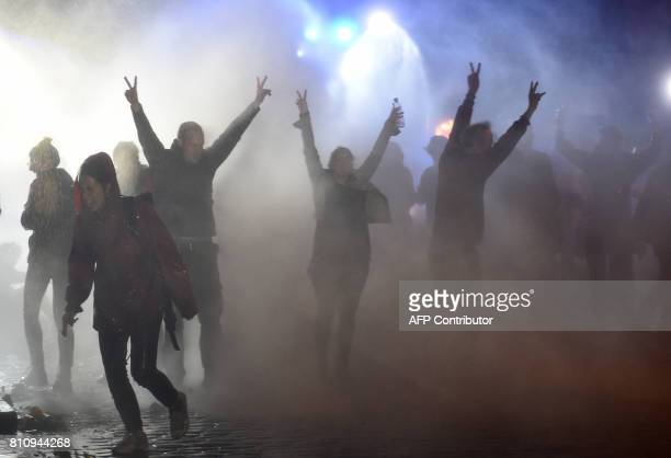 Demonstrators are doused with water cannon by police during riots on July 8 2017 in Hamburg northern Germany after the leaders of the world's top...