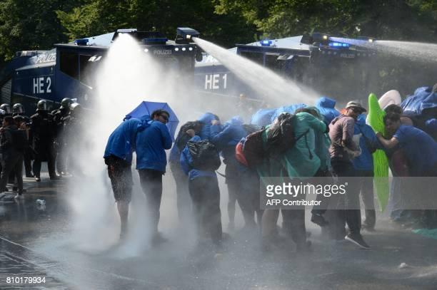 TOPSHOT Demonstrators are hit by water cannons of the police as they protest on July 7 2017 in Hamburg northern Germany where leaders of the world's...