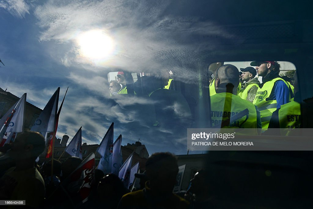 Demonstrators are reflected on a car window as dockers take part in a protest called by the main workers union CGTP against the 2014 State Budget in front of the Parliament in Lisbon on November 1, 2013. Thousands of demonstrators protested in Portugal today against salary cuts and public sector reforms planned in the government's 2014 budget under the country's international bailout deal. After nearly three years of belt-tightening, the budget aims to save a further 3.9 billion euros (5.3 billion USD), partly through cutting public sector salaries and pensions.