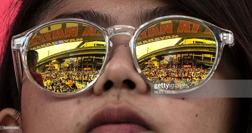Demonstrators are reflected on a woman's shades during a protest to show support to Philippine President Rodrigo Duterte in Manila on June 30, 2016. Authoritarian firebrand Rodrigo Duterte was sworn in as the Philippines' president on June 30, after promising a ruthless and deeply controversial war on crime would be the main focus of his six-year term. / AFP / NOEL