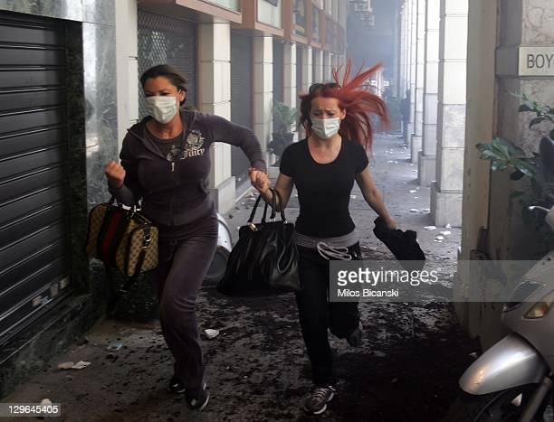 Demonstrators are seen running for shelter from a protest against plans for new austerity measures October 19 2011 in Athens Greece Greece's largest...
