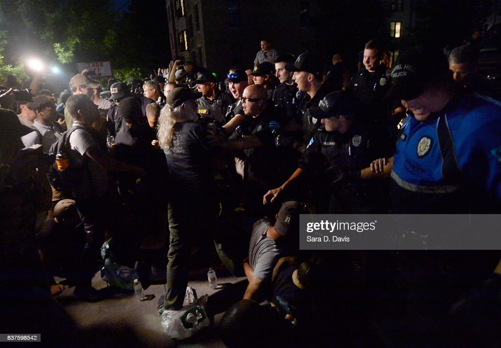 Demonstrators are shoved off a sidewalk and into a blocked street by police during a rally for the removal of a Confederate statue, coined Silent Sam, on the campus of the University of Chapel Hill on August 22, 2017 in Chapel Hill North Carolina.