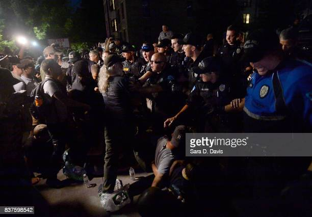 Demonstrators are shoved off a sidewalk and into a blocked street by police during a rally for the removal of a Confederate statue coined Silent Sam...