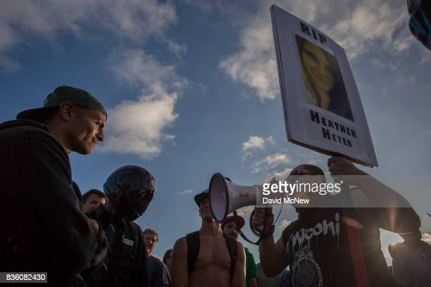 Demonstrators argue with a counter demonstrator holding a sign in memorial to 32yearold Heather Heyer who killed when a man rammed his car into a...