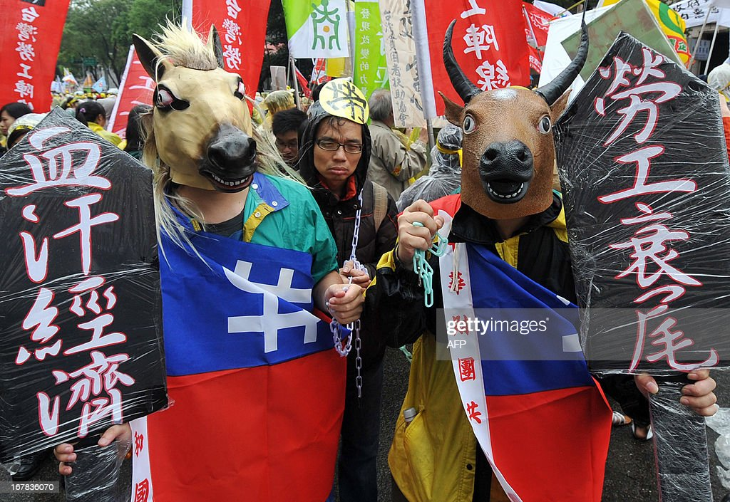 Demonstrators attend a a May Day rally in Taipei on May 1, 2013. More than 10,000 people took to the streets in Taipei to protest the government's planned pension cuts, including raising labour insurance fees and lowering the payment scale. AFP PHOTO / Mandy CHENG