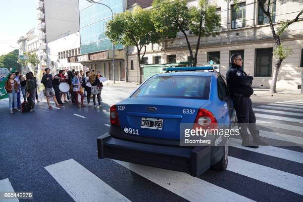 Demonstrators block a roadway while a police officer stands guard during a national strike in Buenos Aires Argentina on April 6 2017 Argentina was...