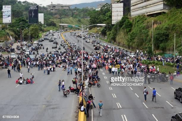 TOPSHOT Demonstrators block the 'Prados del Este' highway one of the major roads in Caracas during a protest against Venezuelan President Nicolas...