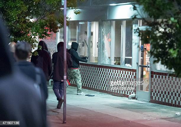 Demonstrators break restaurant windows during a May Day protest in Oakland California on May 1 2015 Hundreds marched throughout the city vandalizing...