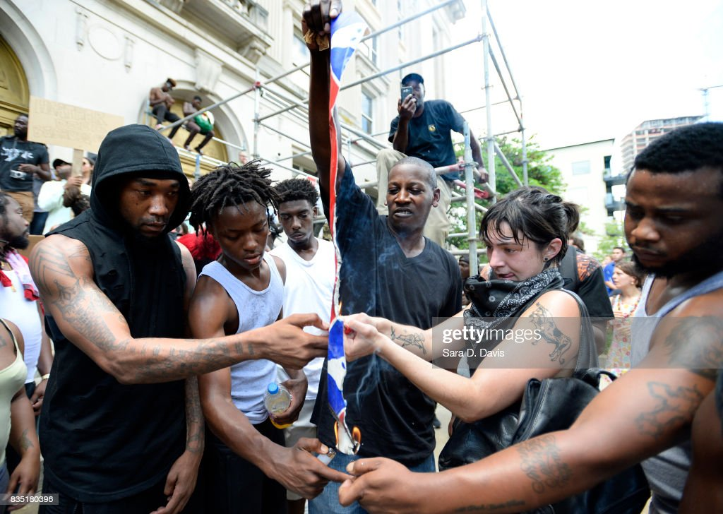 Demonstrators burn a Confederate flag replica in reaction to a potential white supremacists rally on August 18, 2017 in Durham, North Carolina. The demonstration comes a week after a fatal clash during a 'Unite the Right' rally between white supremacists and counter protesters in Charlottesville, Virginia.