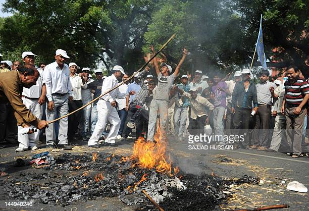 Demonstrators burn an effigy of India's Human Resource Development Minister Kapil Sibal during a protest against the publishing of an allegedly...