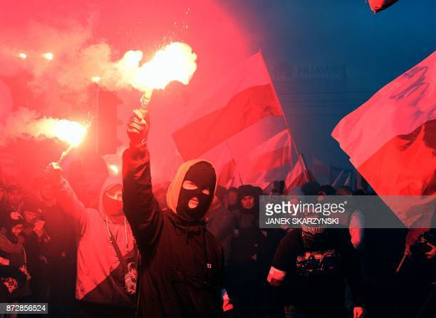 Demonstrators burn flares and wave Polish flags during the annual march to commemorate Poland's National Independence Day in Warsaw on November 11...