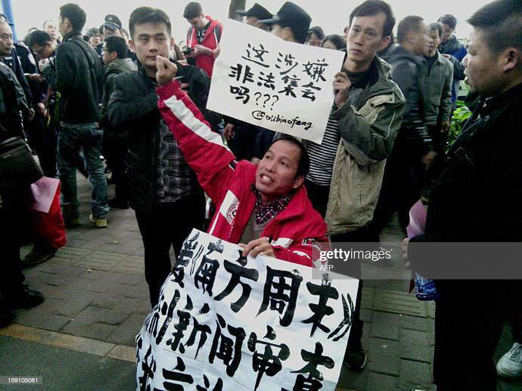 Demonstrators call for press freedom in support of journalists from the Southern Weekend newspaper outside the company's office building in Guangzhou, south China's Guangdong province on January 8, 2013. Chinese bloggers and celebrities along with foreign media campaigners threw their support behind journalists at a newspaper enmeshed in a censorship row on January 8, after a rare protest for press freedom.CHINA