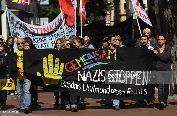 Demonstrators carry a banner that reads 'Stop Nazis Together Dortmund Association Against the Right' while marching to celebrate a court order...